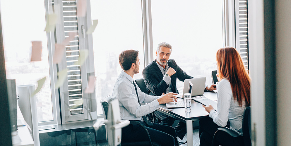 Meeting with two men and a woman in a conference room